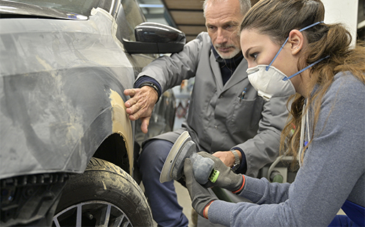 Apprentice working on a car