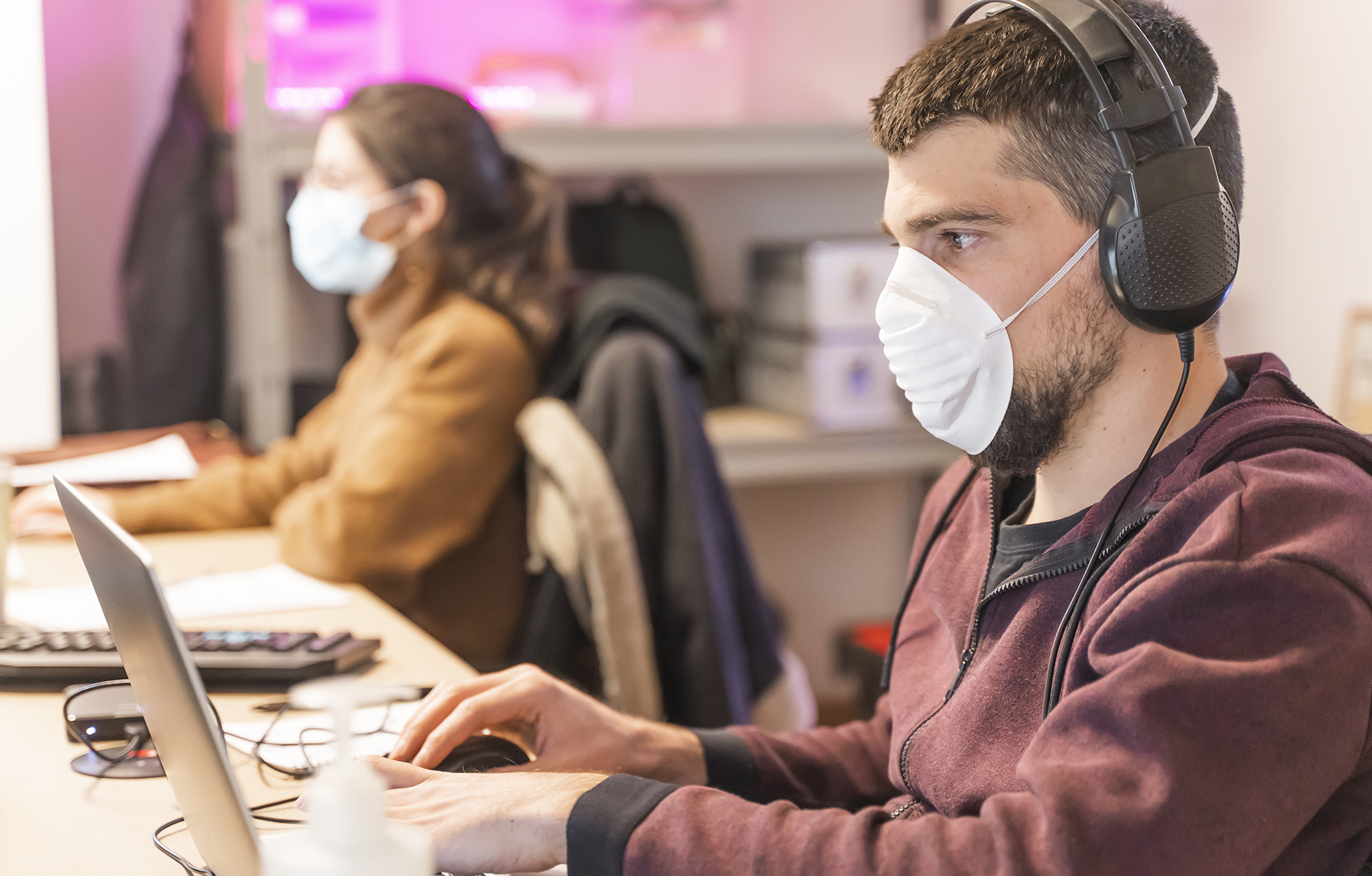 Man working on laptop with mask