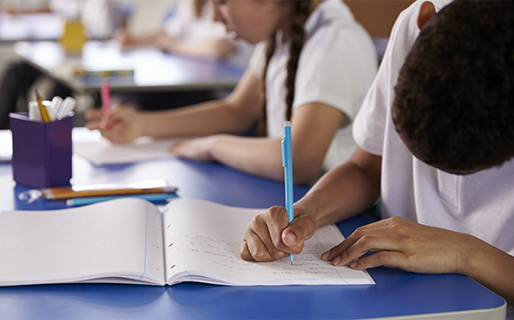 School pupils writing at their desk